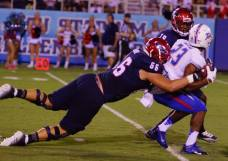 Florida Atlantic's Dillon DeBoer (66) tackles Tulsa's Will Barrow during their game in Boca Raton, FL, on Sept. 13, 2014. (RoadTripSports photo by Kendall Webb)