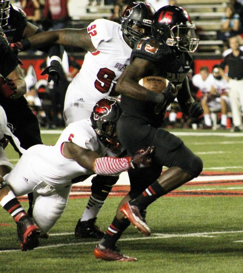Louisiana running back Elijah McGuire (right) runs away from a pair of Arkansas State defenders during their game in Lafayette, La., on Oct. 21, 2014. (RoadTripSports photo by Matthew Postins)