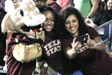 A couple of Texas State fans take a selfie with Boko the Bobcat during their game with Louisiana on Oct. 14, 2014. (RoadTripSports photo by Matthew Postins)