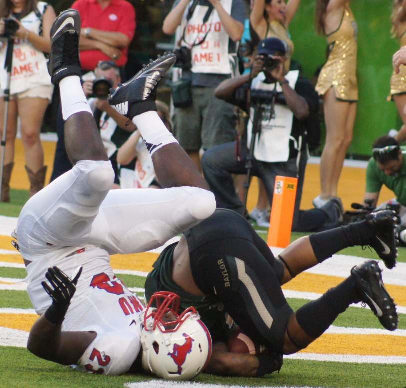 Players from SMU and Baylor go to the ground while fighting for a football in their season opener in 2014. (RoadTripSports photo by Chuck Cox)
