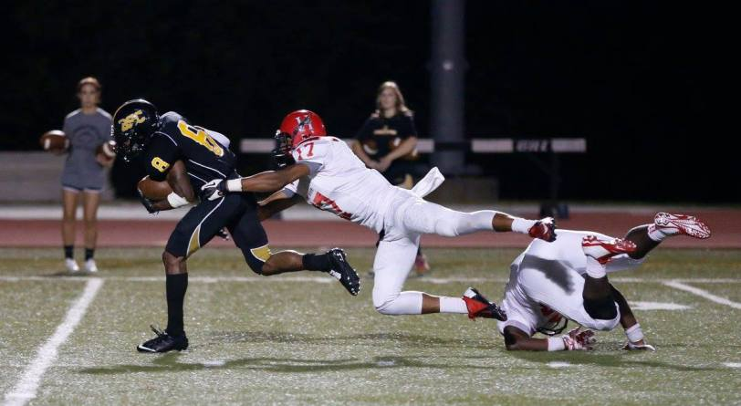 Birmingham-Southern wide receiver Jamal Watkins (left) tries to elude the grasp of Huntingdon's Demetrius Brown during their game on Sept. 12, 2015, in Birmingham, Ala. (RoadTripSports photo by Kendall Webb)