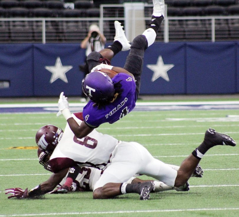 West Texas A&M DB Davontae Merriweather (in white) tackles Tarleton State's Jabari Anderson. (RoadTripSports photo by Matthew Postins)