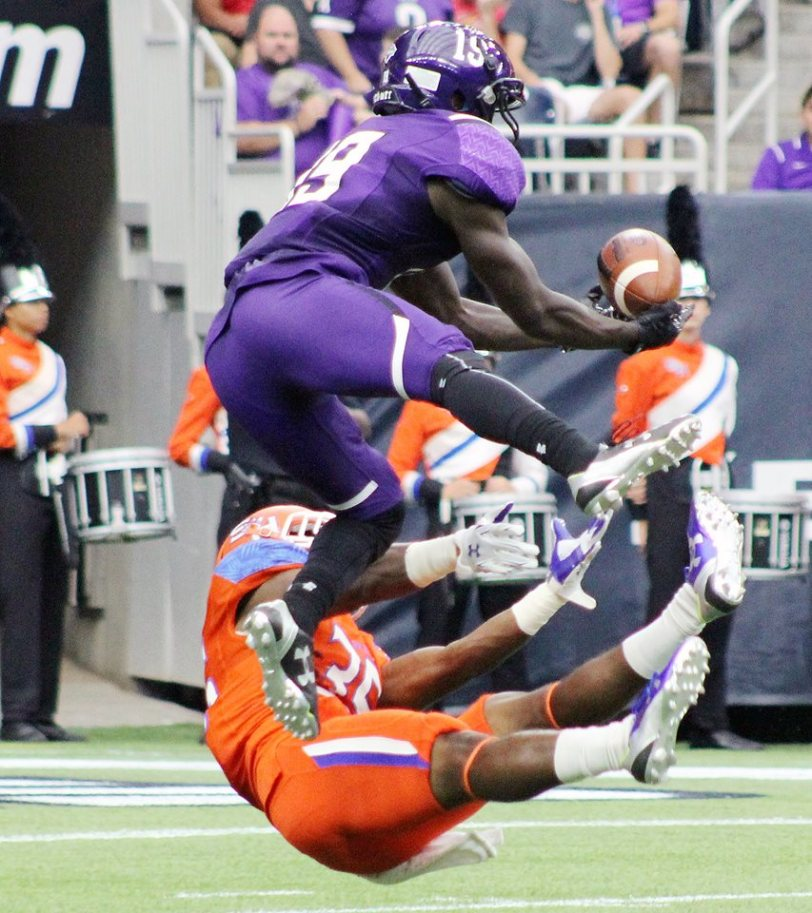 SFA receiver Robert Sylvester (19) leaps over Sam Houston's Cortland Fort (on ground) to make a catch to set up a potential score.