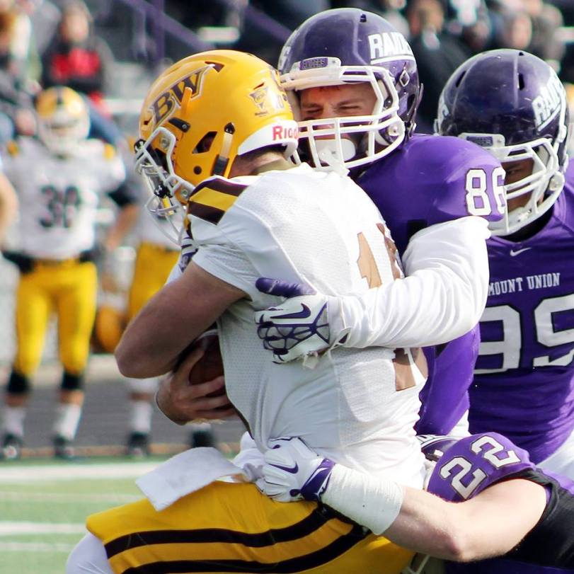 Mount Union's Mike Furda (right) put a big hit on Baldwin-Wallace quarterback Tyler Moeglin on Nov. 7, 2014, in Alliance, OH. (RoadTripSports photo by Matthew Postins)